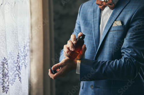 Handsome guy is choosing perfumes, Elegant man in suit using cologne,groom getti Canvas Print