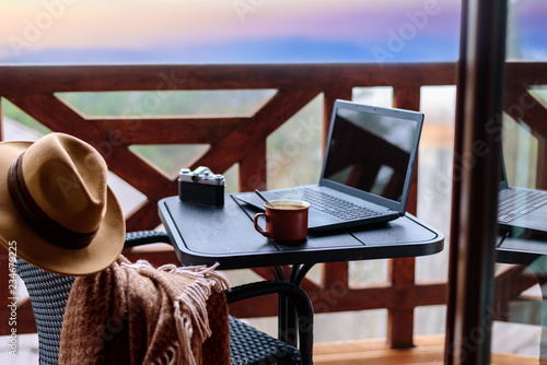 Laptop or notebook, camera, cup on the table. Concept of freelance or remote business, blogger, writer.