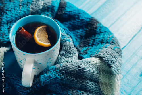 Spoed Foto op Canvas Thee A mug of hot tea with cinnamon on a blue background with a scarf