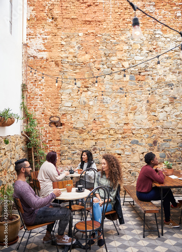 Fototapeta Young people talking over coffee in a cafe courtyard