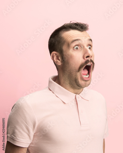 Valokuvatapetti The surprised and astonished young man screaming with open mouth isolated on pink background
