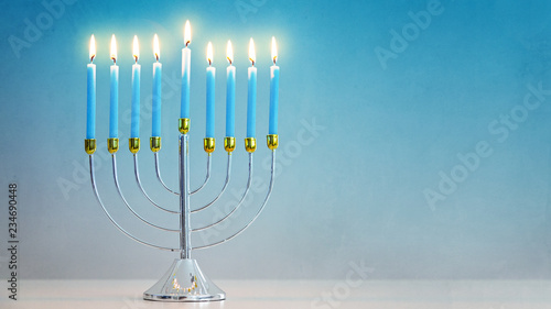 Fotografie, Obraz Illuminated Hanukkah Menorah Blue Background