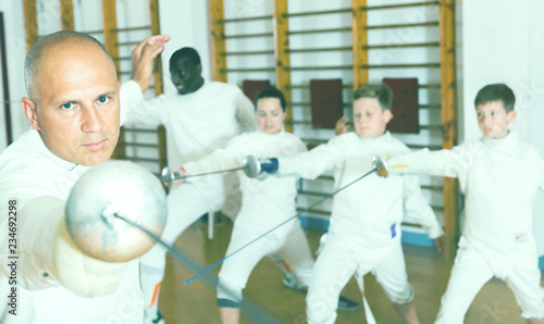 Adult man fencer practicing effective fencing techniques in