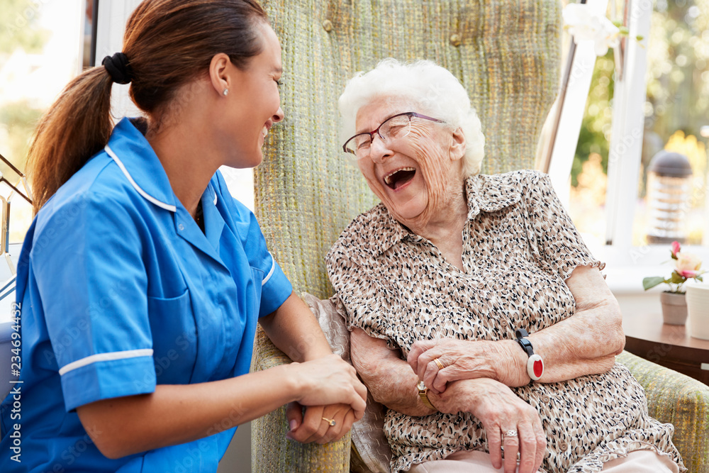 Fototapety, obrazy: Senior Woman Sitting In Chair And Laughing With Nurse In Retirement Home