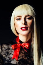Portrait Of A Beautiful Blonde Woman With Red Bow And Black Lace Top. Isolated On Black Studio Background