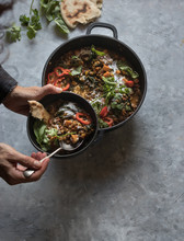 Person Holding Bowl Near Pot With Ragout Of Lentil And Sweet Potato Curry