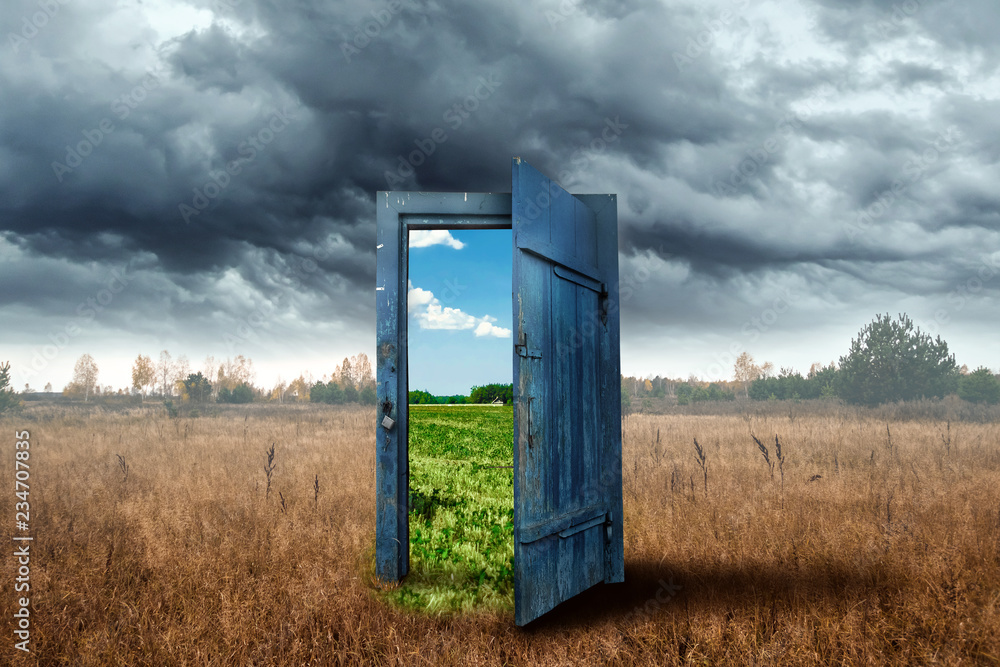 Fototapeta Creative background. Old wooden door, blue color, in the box. Transition to a different climate. The concept of climate change, portal, magic. Copy space.