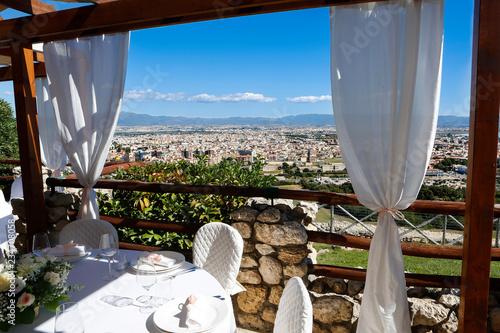 Obraz na plátně apparecchiatura di tavoli con vista spettacolare di Cagliari dall'alto