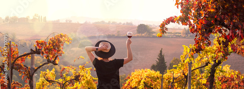 Photo Stands Wine Girl in a hat at sunset and a glass of wine in hand. Nature Italy, hills and grape fields the sunlight. Glare and sun rays in the frame. Free space for text. Copy space.