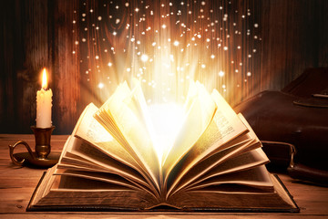 Altes Buch mit magischen Lichtern auf Holztische bei Kerzenschein