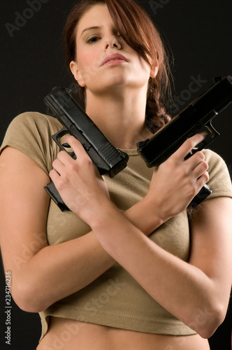 фотография  Young woman holding two guns across her chest
