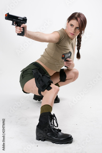 фотография  Young brunette woman with two guns squatting down