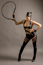 Young Woman Wearing A Cat Suit And Mask With A Whip