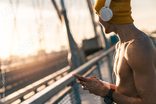 Handsome shirtless sportsman using phone while listening to music at