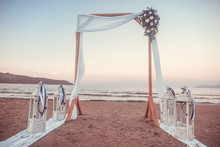 Wedding Ceremony On A Tropical Beach In White. Arch Decorated With Flowers On The Sandy Beach. Wedding Concept (color Toned Image)