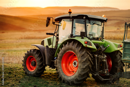 Close-up details of tractor and trailer on hills at sunset