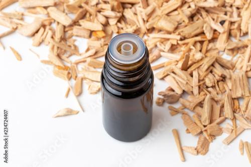 Valokuva  A bottle of cedar essential oil with pieces of cedar wood