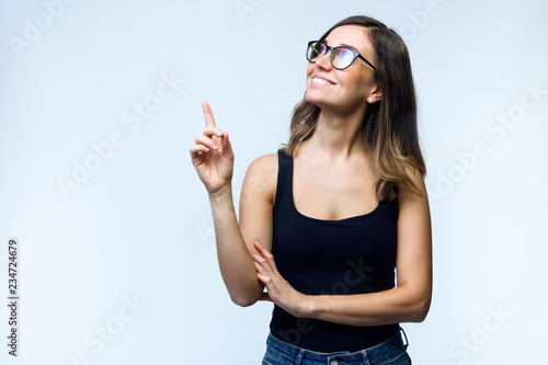 Fotografía  Beautiful young woman with eyeglasses showing and pointing over white background