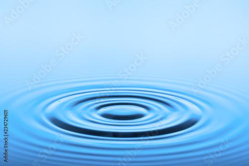 Fotografija  blaue Wasseroberfläche mit kreisförmigen Wellen
