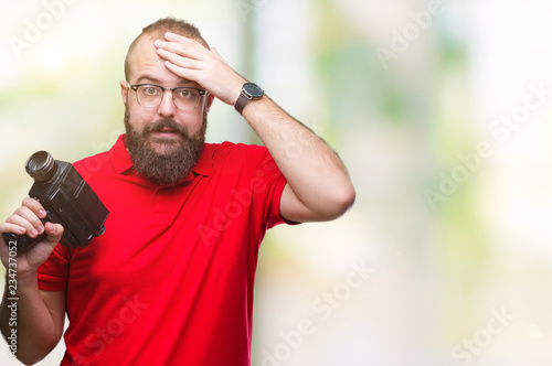 Obraz na plátne Young caucasian hipster man filmming using retro video camera over isolated background stressed with hand on head, shocked with shame and surprise face, angry and frustrated