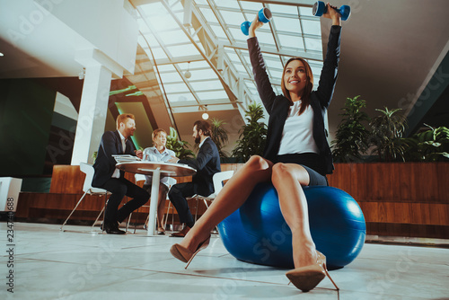 Woman Balance on Ball with Dumbbells in Office