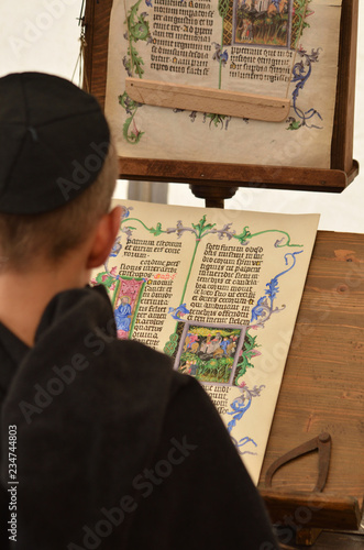 Photo Young male medieval scribe make manuscript - calligraphy