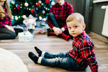 Parent And Little Children Near Christmas Tree Indoors. Christmas Family Give Gift Present Box, Night Xmas. Merry Christmas And Happy Holidays! Family Exchanging Gifts.