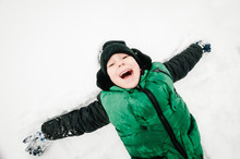 Happy Boy Portrait Walking, Playing And Lie In The Snow In Winter Park, Concept Of A Holiday. Emotions Of Happiness. Flat Lay, Top View.