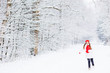 a cute girl in stylish winter clothes running and smiling agains