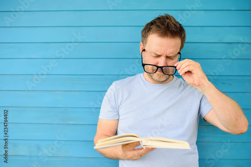 Portrait of mature man with big black eye glasses trying to read book but having Wallpaper Mural