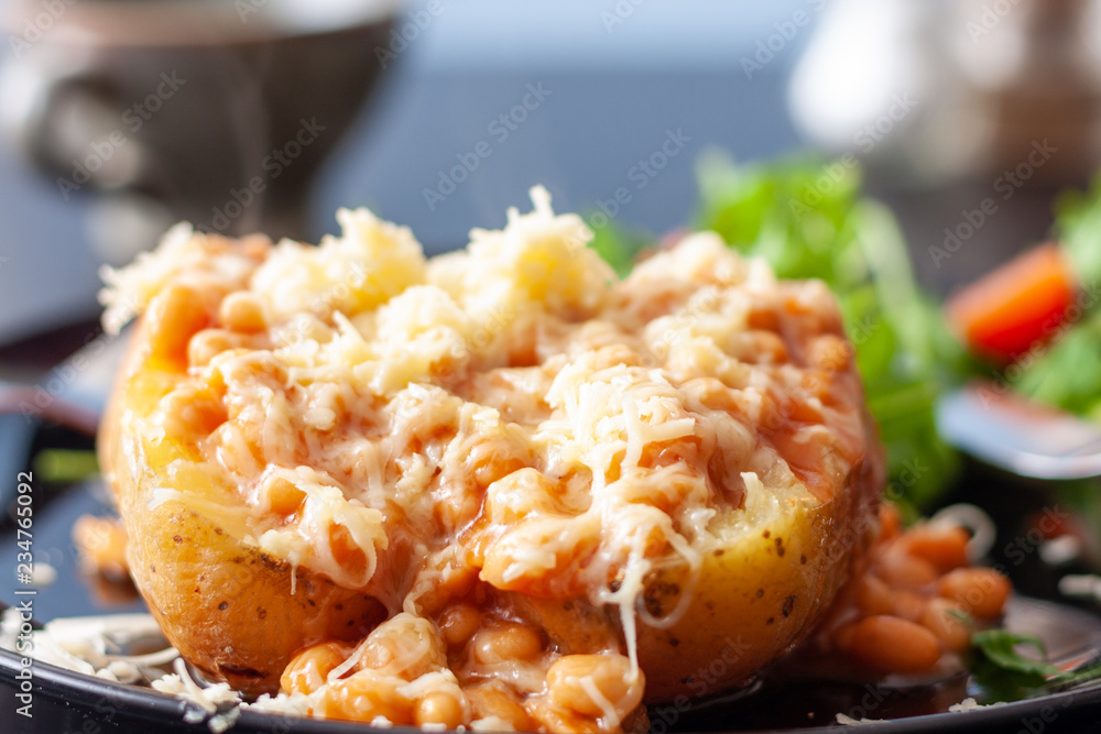 Fototapeta A baked potato topped with baked beans and cheese, served with a salad