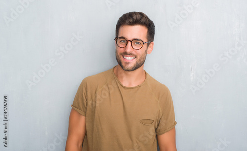 Obraz Handsome young man over grey grunge wall wearing glasses looking away to side with smile on face, natural expression. Laughing confident. - fototapety do salonu