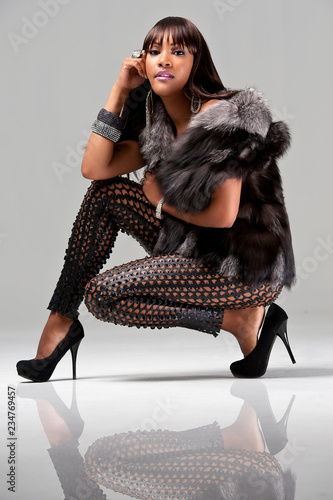 Young african-american woman wearing a fur jacket Wall mural