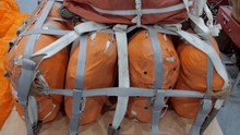 On The Wooden Pallet There Are Several Orange Bags With Things And Equipment Fastened With A Strap And With A Laid Parachute On Top, Ready To Be Dropped From An Airplane. Shot In Motion