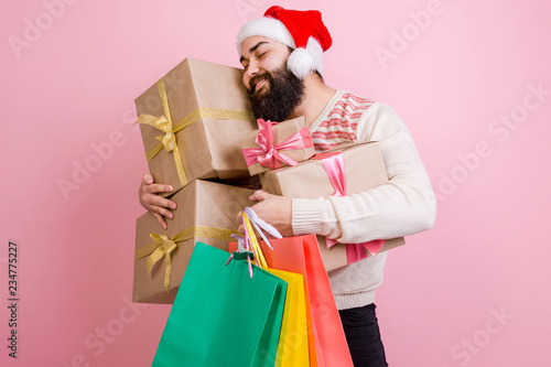 Fotobehang Art Studio Happy man in Santa's hat holding a lot of gift boxes with colored packages pressed to him