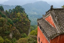Red Taoist Monastery And Temple Built On The Side Of A Mountain With Fall Foliage And Lush Vegetation Surrounding, In China