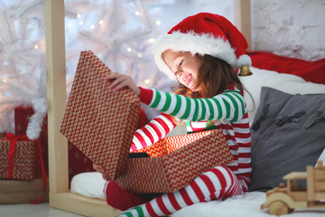 Fototapeta happy child in pajamas with christmas gifts