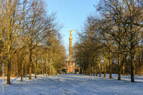 Fotografie, Obraz  Diminishing perspective view of snow covering pathway and tree without leaves in Tiergarten and background of Victory Column in Berlin, Germany