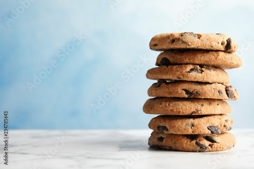 Stack of tasty chocolate chip cookies on table. Space for text