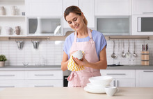 Woman Wiping Ceramic Cup At Table With Clean Dishes In Kitchen