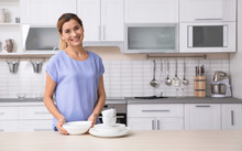 Woman With Clean Dishes Near Table In Kitchen. Space For Text