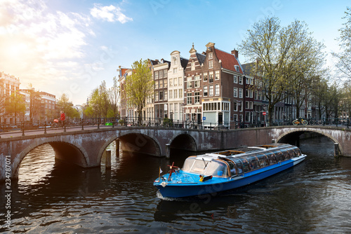 Fotografija Amsterdam canal cruise ship with Netherlands traditional house in Amsterdam, Netherlands