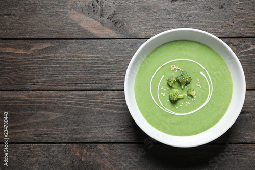 Fresh vegetable detox soup made of broccoli in dish and space for text on wooden table, top view