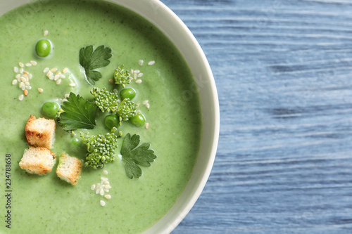 Fresh vegetable detox soup made of green peas and broccoli in dish on wooden background, top view with space for text