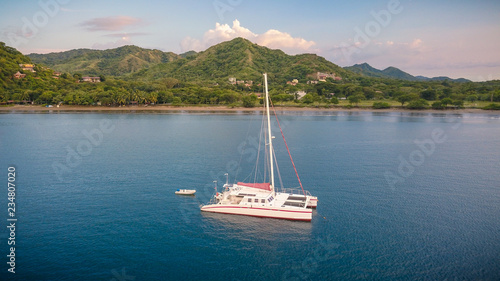 A nice drone shot of a large white catamaran yacht anchoring in a beautiful blue bay in front of an empty beach on the green coast of Costa Rica in Central America Wallpaper Mural