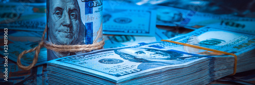 Fotografía  A roll of dollars with a pack of dollars against a background of scattered hundred dollar bills in blue light