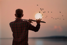 Man Playing Flute With Sunset Or Sunrise Background