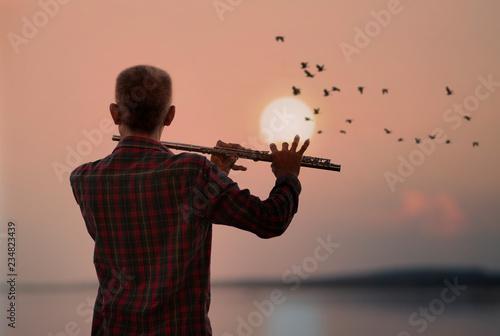 Obraz na plátne Man playing flute with sunset or sunrise background