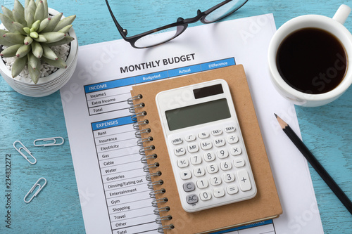 Fototapeta Monthly budget with white calculator on blue table obraz
