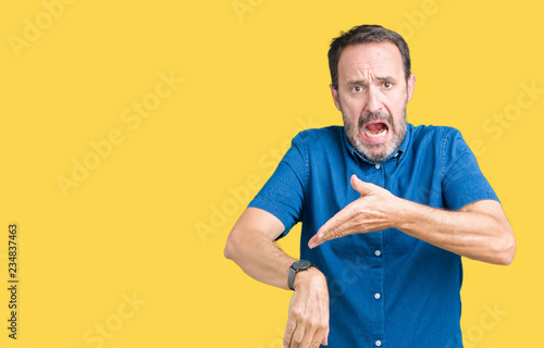 Fototapeta Handsome middle age elegant senior man over isolated background In hurry pointing to watch time, impatience, upset and angry for deadline delay obraz
